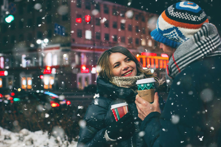 Real young couple walking together in night city under snow, kissing and smiling, winter romance, lifestyle Winter Smiling Happiness Cold Temperature Warm Clothing Clothing Portrait Snow Emotion Young Adult Snowing Holiday Hat Christmas Adult City Architecture Headshot Holding Scarf Positive Emotion