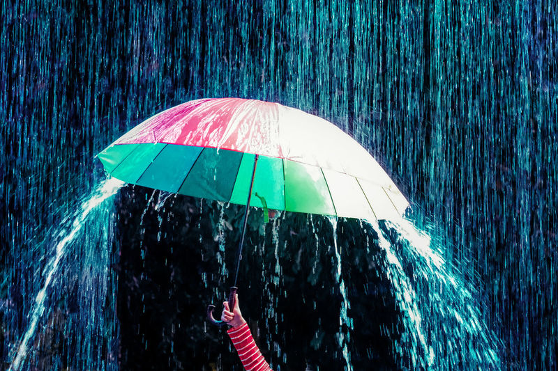 Cropped hand of woman holding umbrella during monsoon