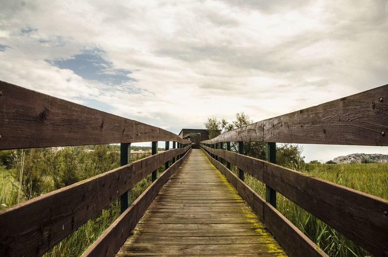 Footbridge over water against sky