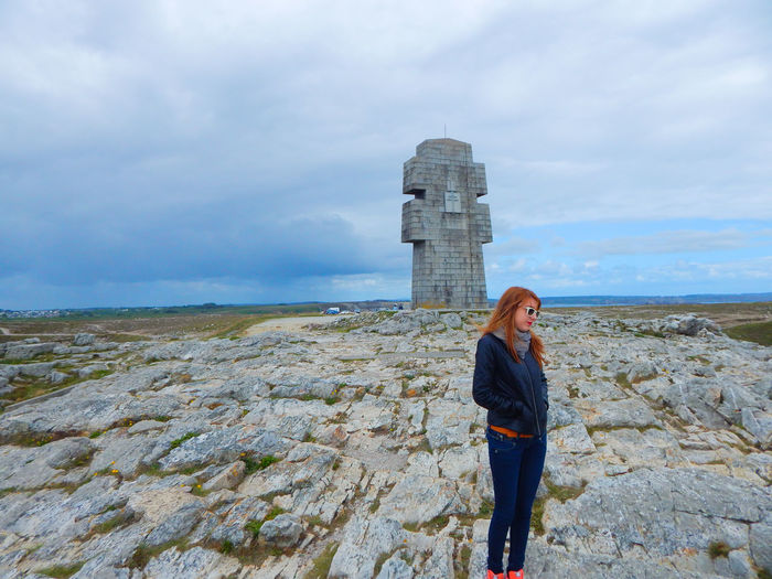 Full length of woman on rocky field by built structure against cloudy sky