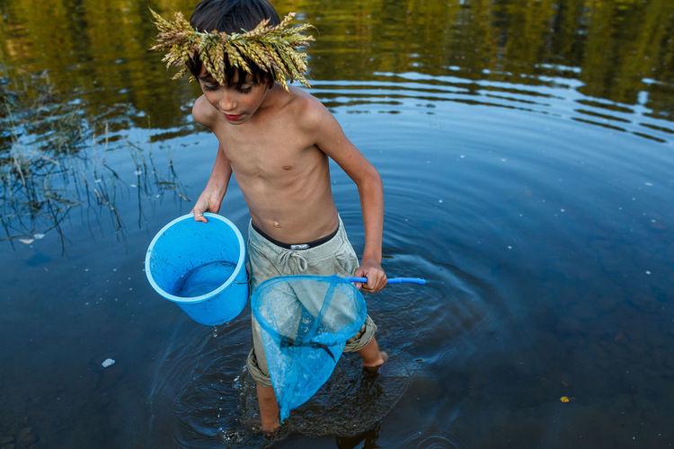Shirtless boy fishing in lake