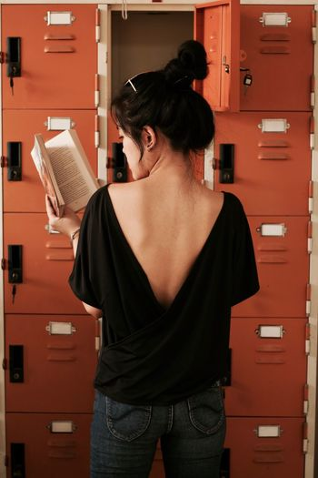 Rear view of young woman reading book while standing by locker