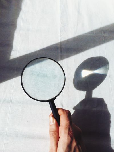Cropped image of person holding magnifying glass