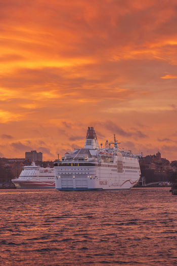 STOCKHOLM, SWEDEN - DEC 30, 2016: Cinderella from the Viking Line company embarking to the port in Stockholm. With a great orange evening sky. Architecture Cinderella City Cityscape Day Gab Harbor Modern Nautical Vessel No People Outdoors Sea Sky Skyscraper Stockholm Sunset Travel Urban Skyline Vertical Water
