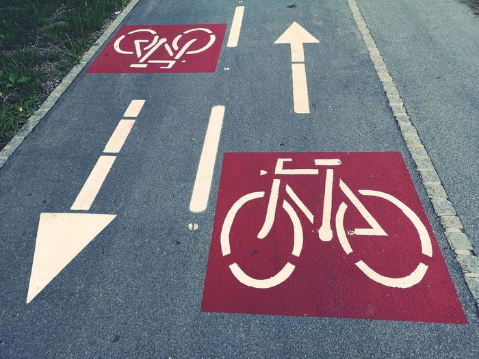 High angle view of arrow symbols with bicycle lane sign on road in city