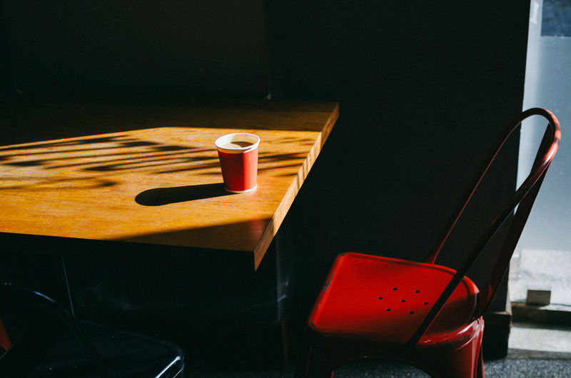 High angle view of coffee cup on table by chair in cafe