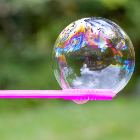 Life in a bubble Bubble Bubble Wand Childs Toy Focus On Foreground Fragility House Large Bubble Life In A Bubble Multi Colored Reflection