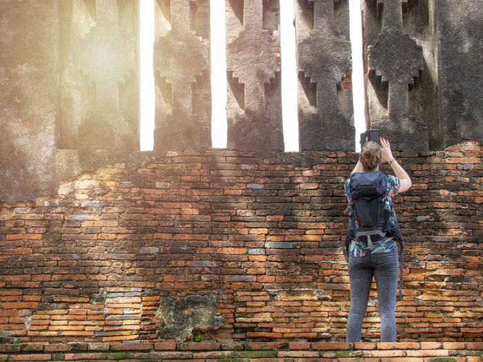 Rear view of woman standing against brick wall