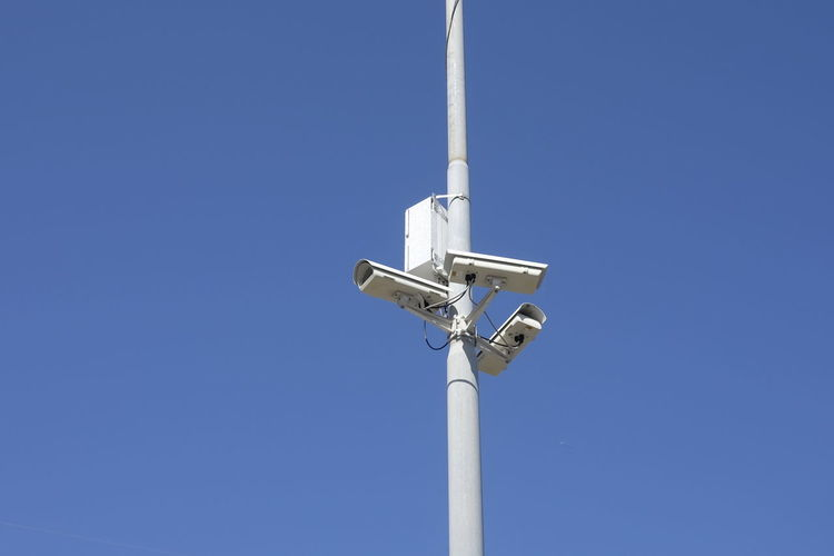 Low Angle View Of Security Camera On Pole Against Sky