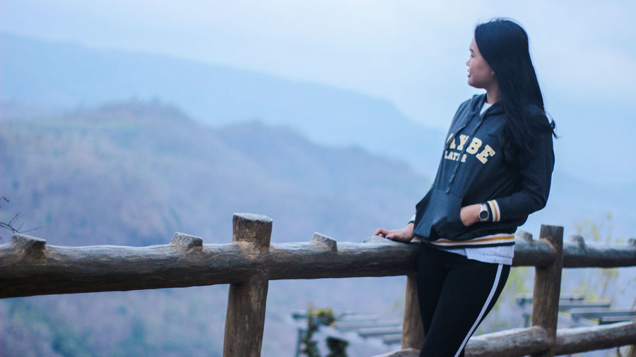 Side view of young woman standing by railing against mountains and sky