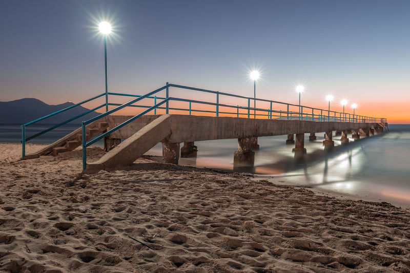 Footbridge over sea against clear sky during sunset