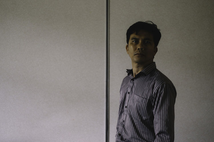Side View Portrait Of Mid Adult Man Standing By Wall
