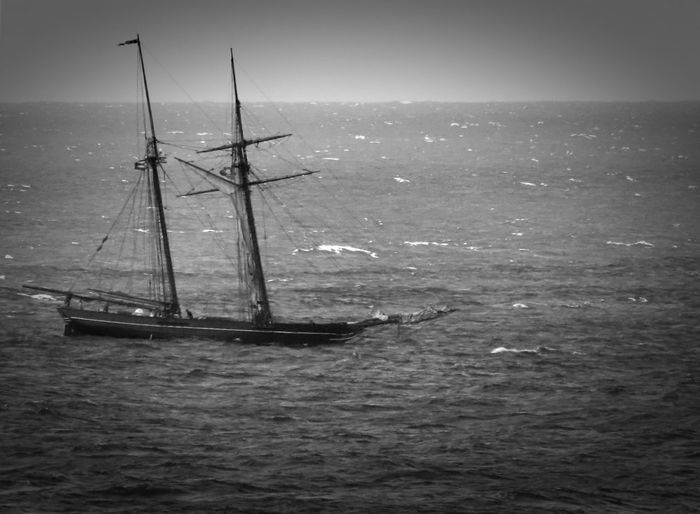 Sailboat on the ocean with a clear sky rendered in black and white Sea Nautical Vessel Water Horizon Over Water Sailboat Mode Of Transportation Horizon Sailing Transportation Sky Beauty In Nature Nature Waterfront Tranquil Scene Scenics - Nature Day Tranquility Mast No People Outdoors