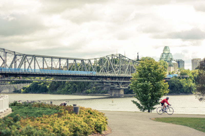 Architecture Bicycle Bridge Bridge - Man Made Structure Built Structure City Cloud - Sky Connection Cycling Day Helmet Land Vehicle Men Mode Of Transport Nature One Person Outdoors Real People Riding River Road Sky Transportation Tree Water