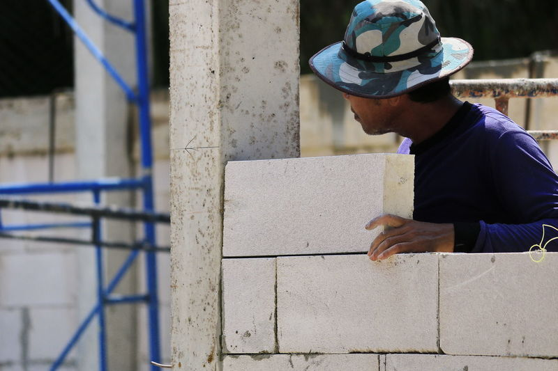 Construction technicians are building brick walls with lightweight bricks. Masonry Work Mason Brickwork  Cement Brick Brick Building Concrete Working Tool Hammer Structure Material Saw Cut Industry Shadow Process Hand Row Many Building Decoration Construction Site Architecture Cap