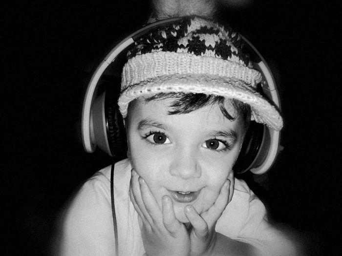 Portrait Of Boy Listening To Music Through Headphones Against Black Background