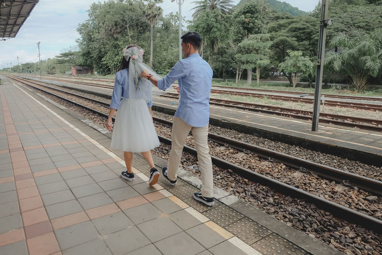 Rear view of people standing on railroad station platform