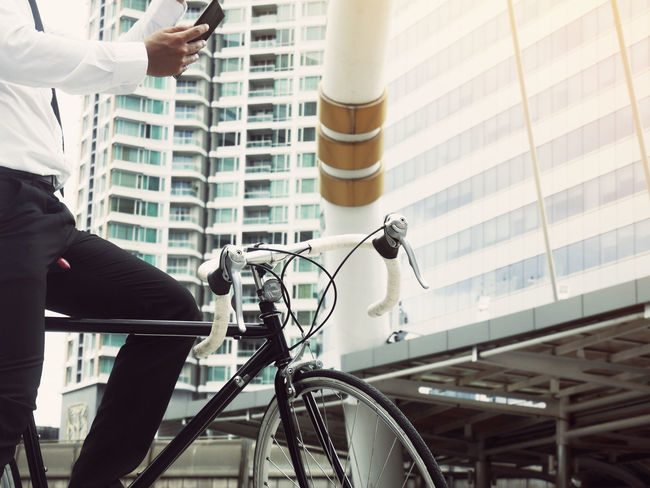Business man riding bicycle go to worker. Activity Architecture Bicycle Building Exterior Built Structure City Day Focus On Foreground Hand Human Body Part Land Vehicle Lifestyles Men Mode Of Transportation Outdoors People Real People Riding Sport Transportation