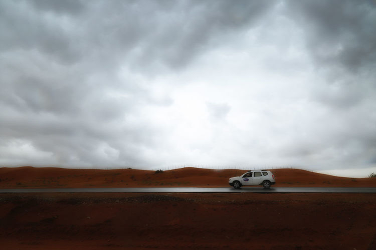 Car Moving On Wet Road Against Cloudy Sky