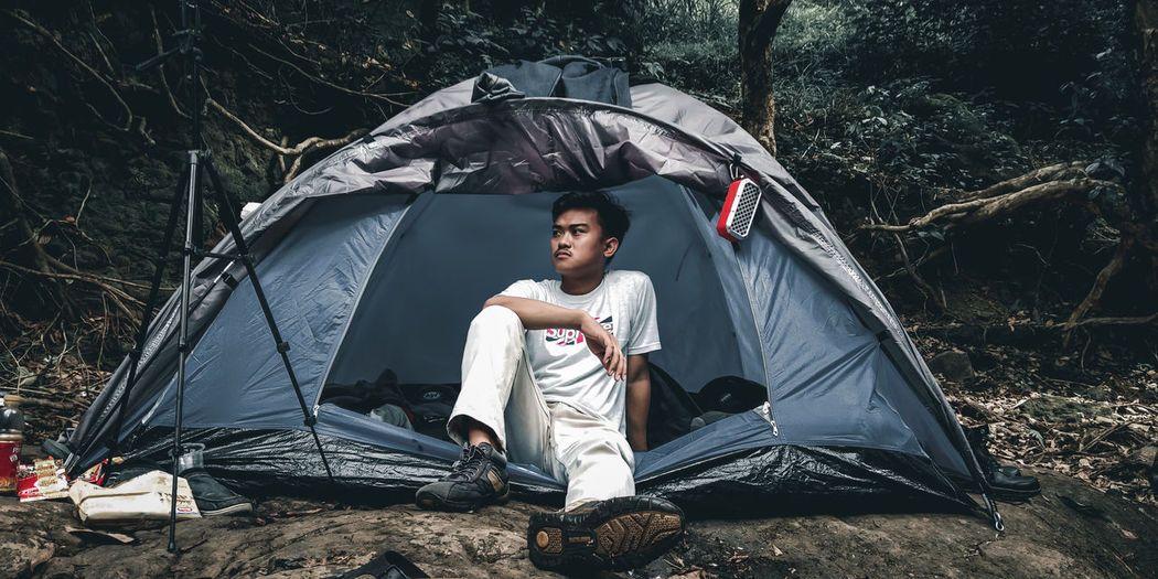 Portrait of young man sitting at tent