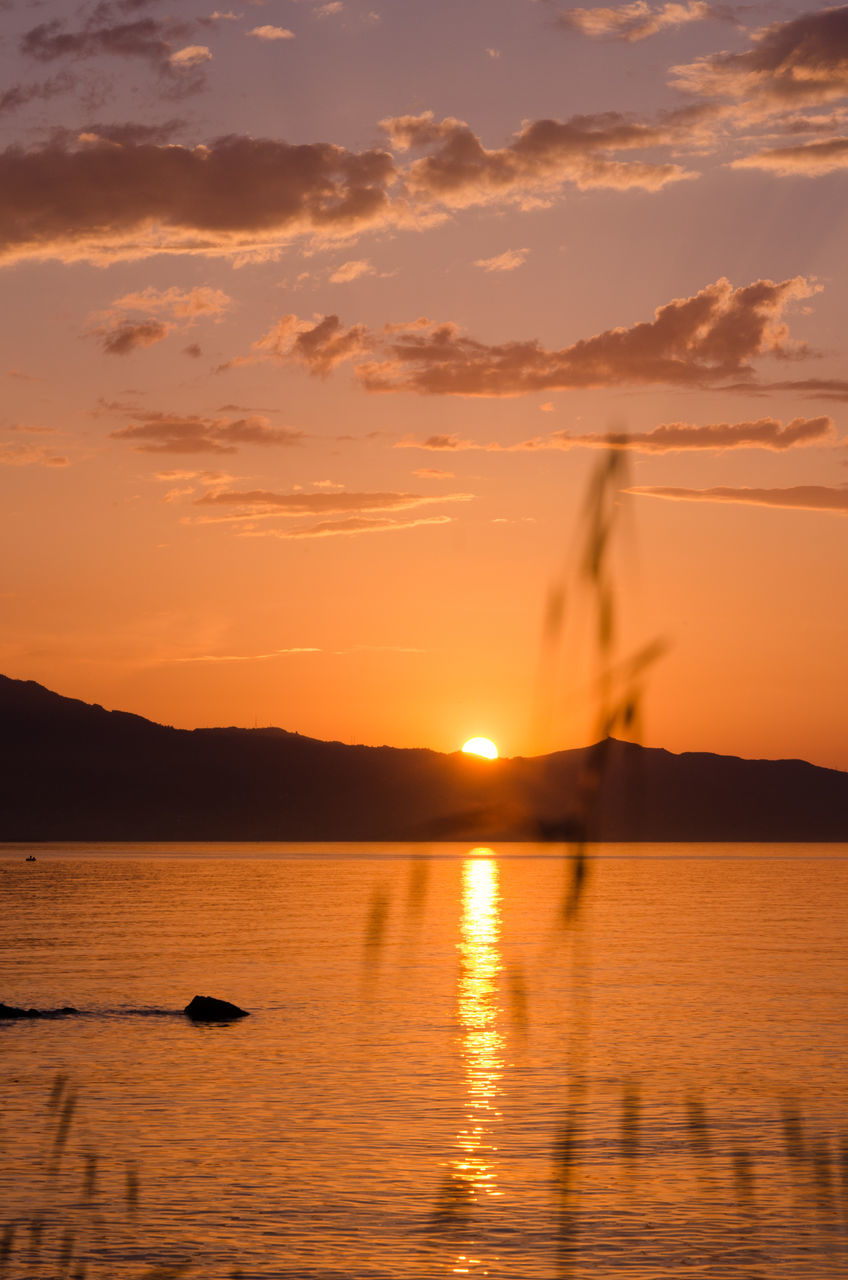 sunset, water, silhouette, beauty in nature, orange color, nature, sky, scenics, sun, reflection, sea, sunlight, nautical vessel, tranquility, tranquil scene, waterfront, outdoors, mountain, sailing, sailboat, no people