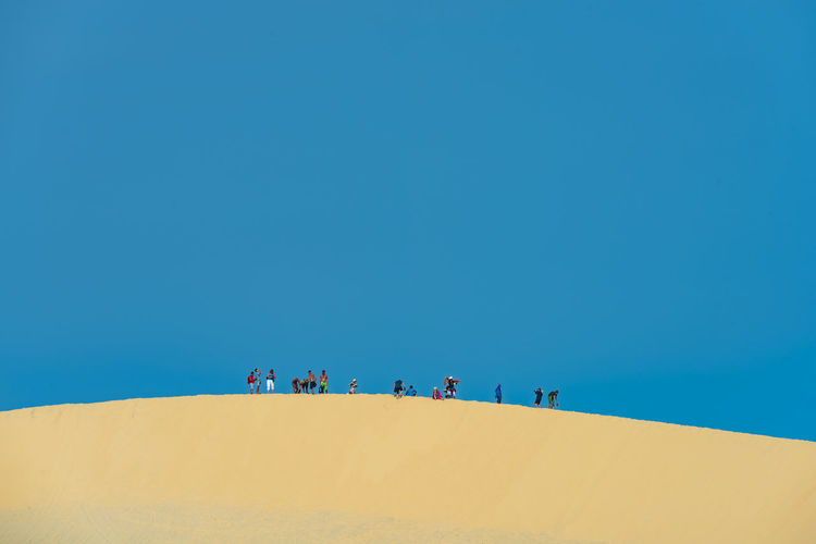 Low angle view of people on sand dune at desert against clear blue sky