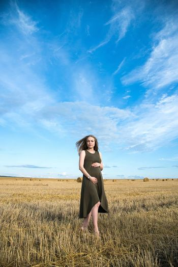 Pregnant woman standing on field against sky