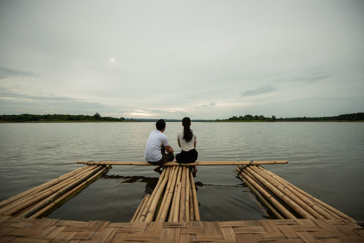 Couple sitting on wooden raft in lake against sky