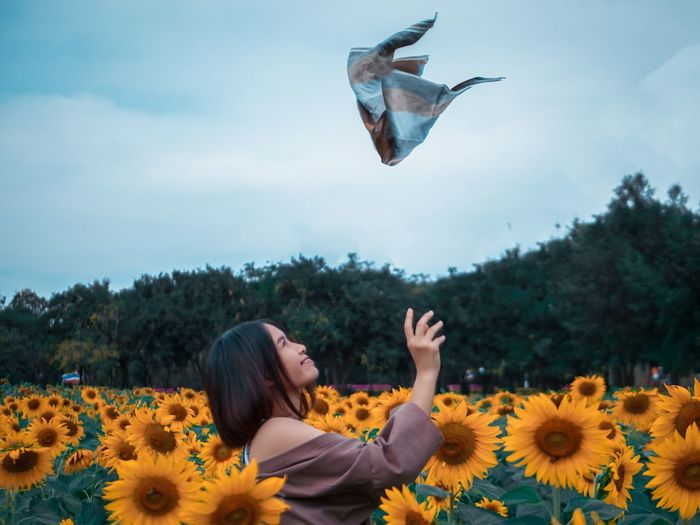 Side view of woman catching scarf while standing on sunflower against sky