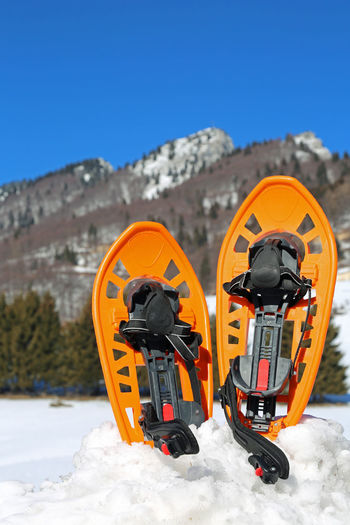 two plastic modern snowshoes in winter in mountains Adventures Excursion Snowshoe Winter Adventure Cold Equipment Extreme Sports Mountains Shoes Snow Snow Shoe Snow Shoe Paws Snow Shoes Snowshoe Trip Snowshoeing Snowshoes Sport Sport Equipment Sporting Sportwear