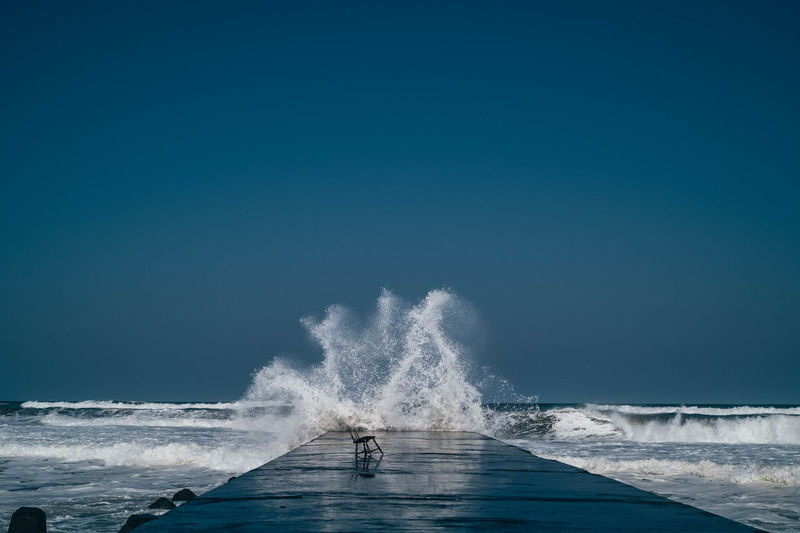 Waves splashing on sea against clear blue sky