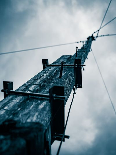 Low angle view of pole with steel cables against sky
