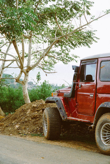 Landscape view of a parked red jeep. Jeep Life Lombok-Indonesia Red Transportation Travel Traveling Car Day Dirtycar Jeep Lombok No People Outdoors Roadtrip Stationary Tree