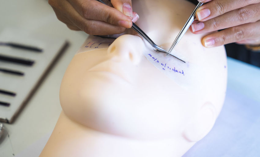 High angle view of hand sticking artificial eyelashes on mannequin