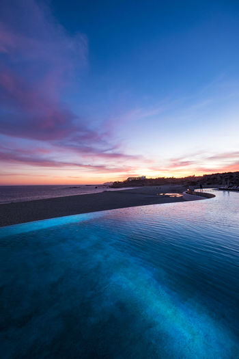 High angle view of infinity pool by beach at sunset