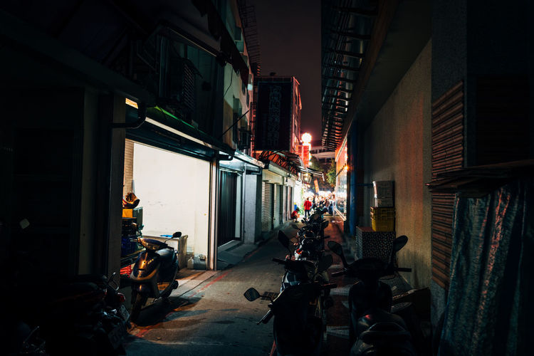 Vehicles in alley amidst buildings at night