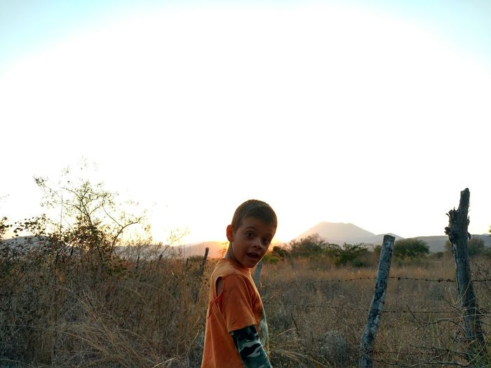Portrait of boy standing on field against clear sky during sunset