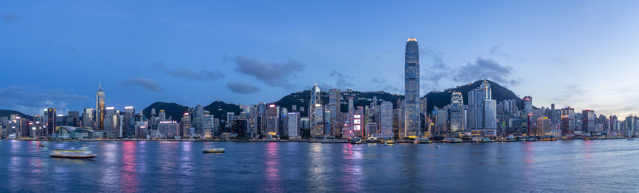 Panoramic view of illuminated buildings by sea against sky