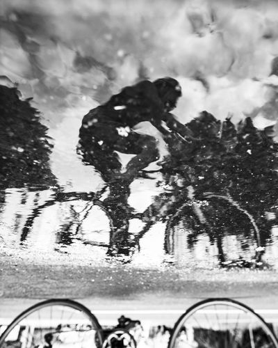 Race bike drivers reflection in a puddle. Asphalt Bicycle Blackandwhite Clouds And Sky Day Mode Of Transportation Nature Outdoors Plant Puddle Race Bike Real People Reflection Sport Streetphotography Tree Water Wet