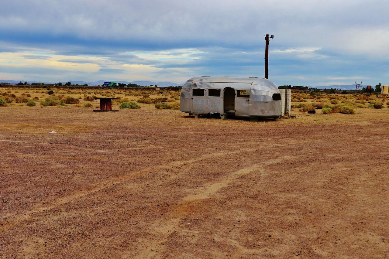 Old Travel Trailer At Desert Against Sky