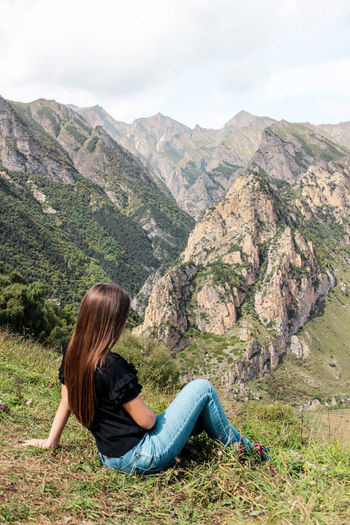 Woman sitting against mountains