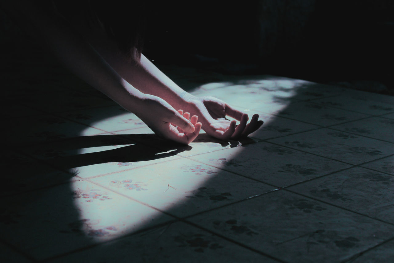 Cropped hands of woman on tiled floor