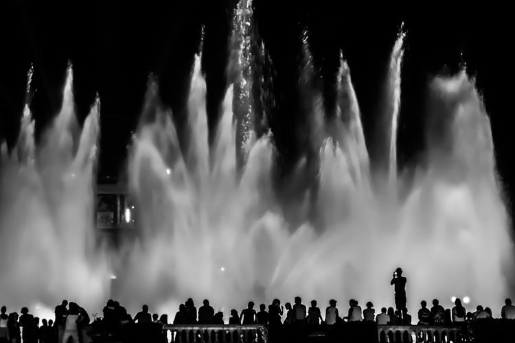 People against fountain at night