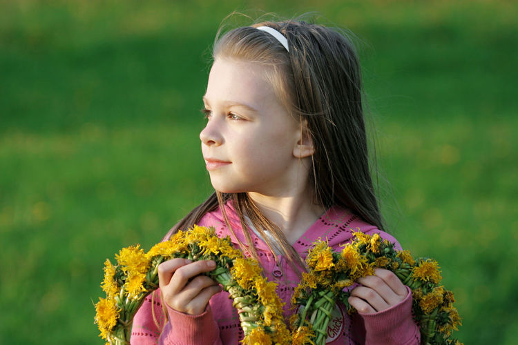 Cute girl holding wreaths outdoors