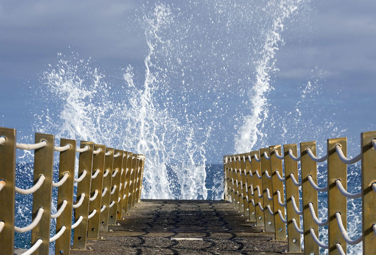 Waves splashing at pier over sea against cloudy sky