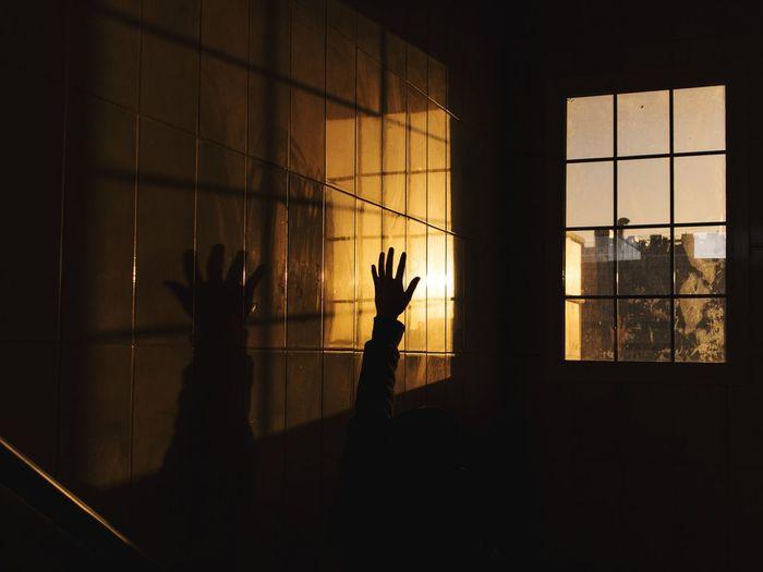 Silhouette people standing by window in dark room