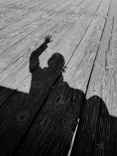 Shadow of people on boardwalk