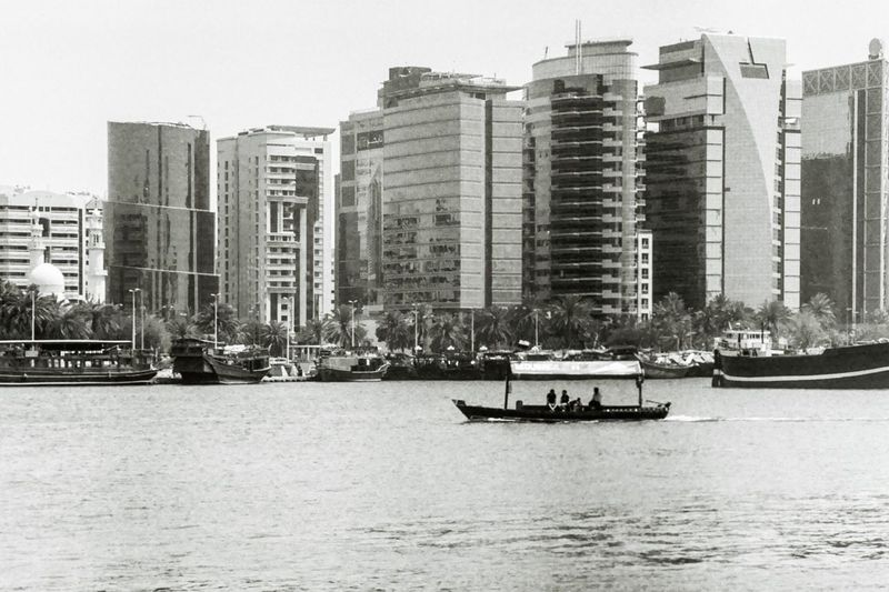Boats sailing on river amidst buildings in city