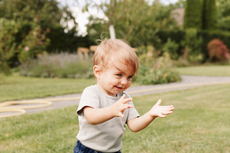 Close-up of cute baby boy standing on field