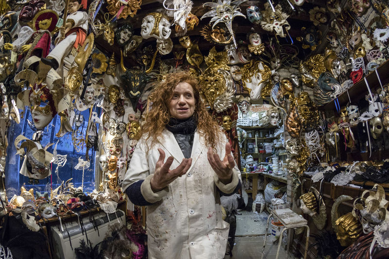 Low Angle View Of Woman Smiling While Standing Amidst Masks In Store